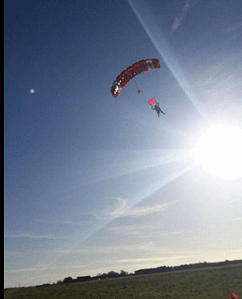 A parachute against blue sky with sun's rays