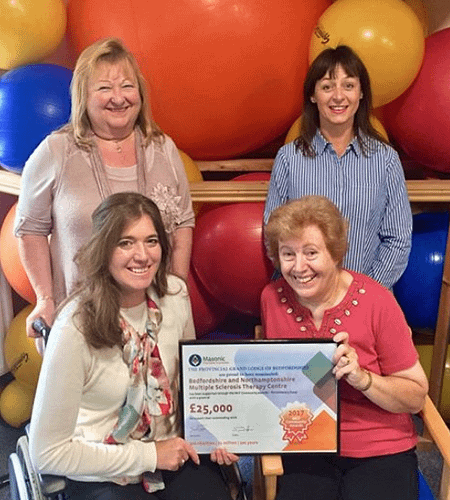 Four ldies, two standing and two seated in front of colourful gym balls, holding a framed cheque for £25, 000