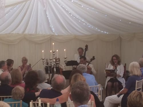 Musicians in a white marquee with a candelabra