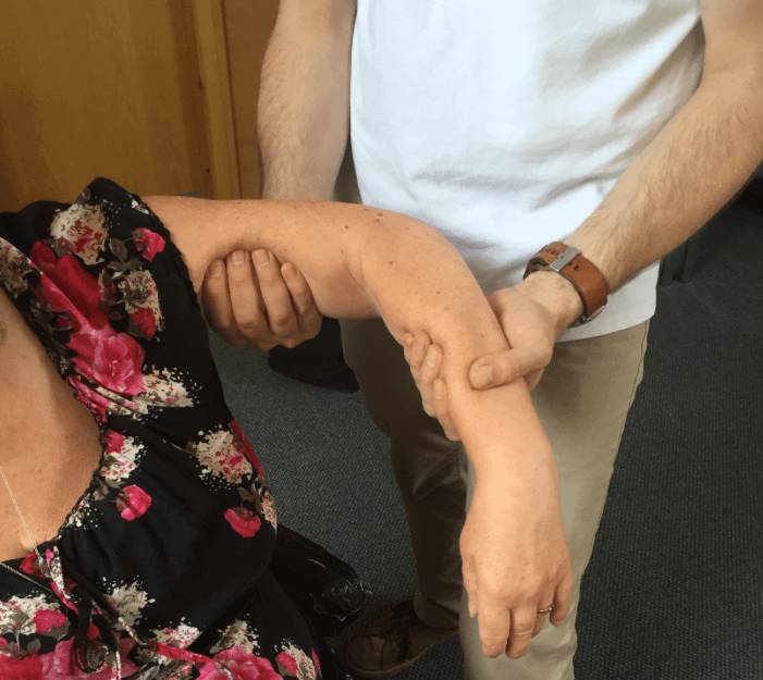 Bowen therapist working on the arm of a person sitting in a wheelchair