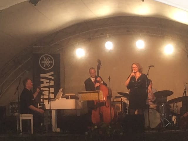 A man playing a white piano, one on double bass and lady in a black dress singing